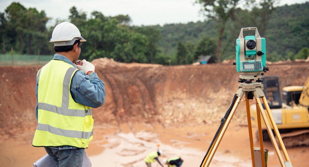 geodeta podczas pomiaru na budowie