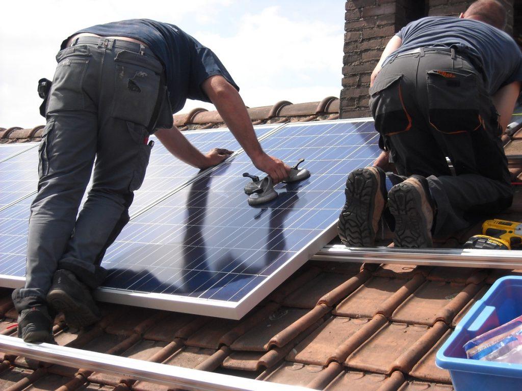 pracownicy montują panele słoneczne