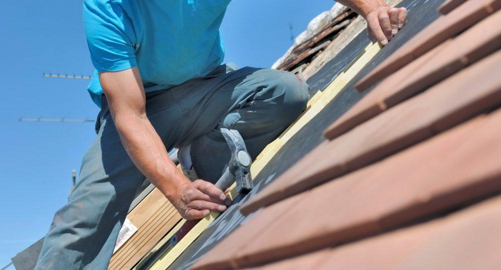 budwlaniec układający membranę na dachu