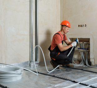 montaż ogrzewania przez pracownika budowy