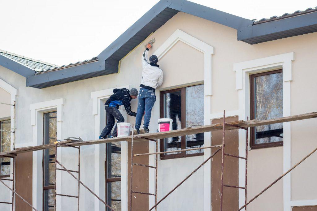 malarze na budowie malujący fasadę budynku