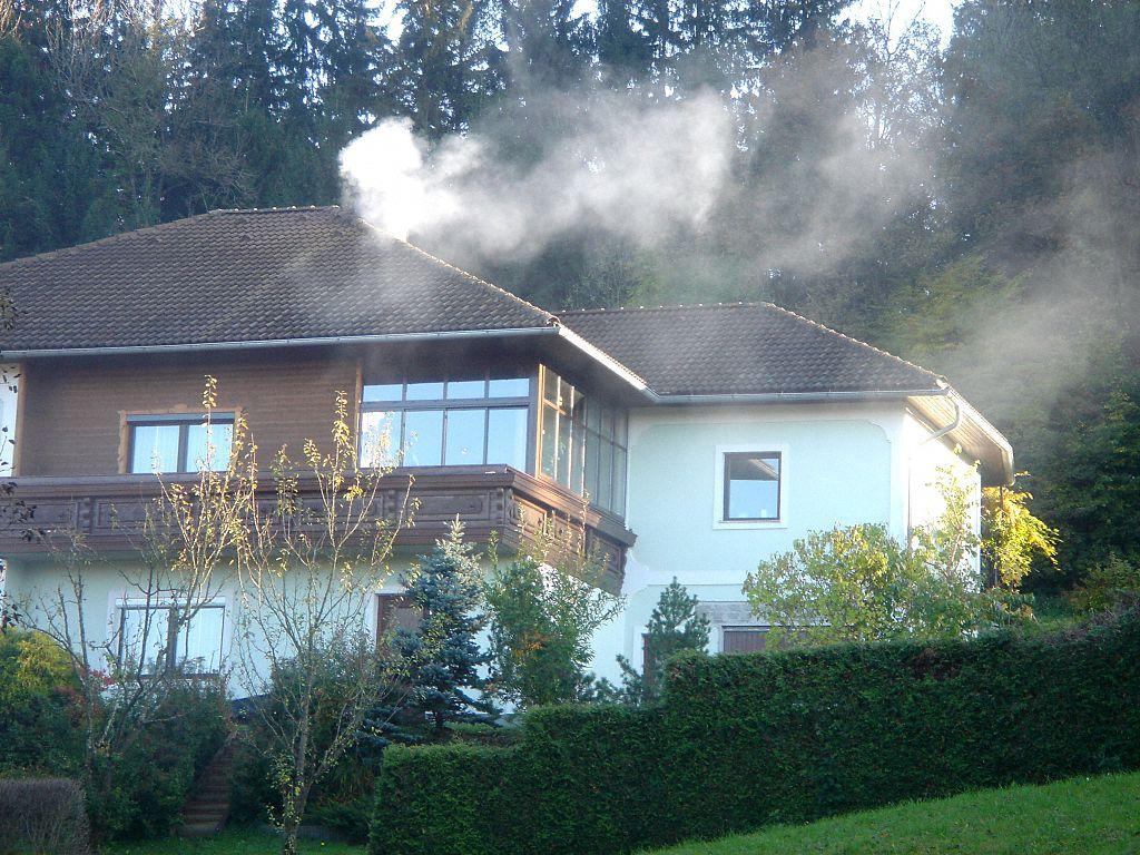 dom jednorodzinny z dymiącym kominem