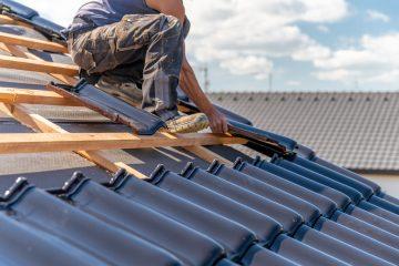 dekarz na dachu układający dachówkę
