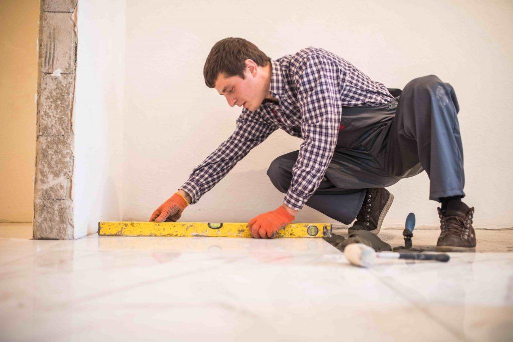 mężczyzna z poziomicą przygotowuje się do układania płytek