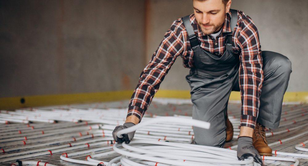 mężczyzna układający ogrzewanie podłogowe